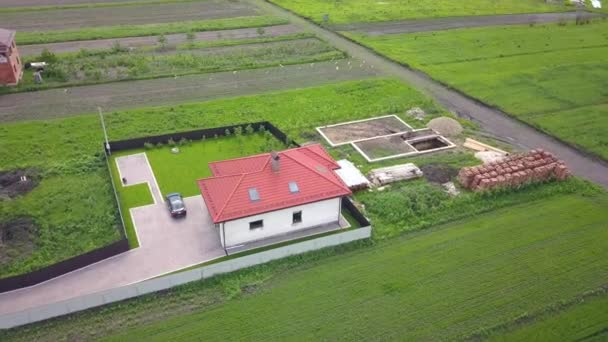 Aerial view of a private house and a yard with fence around.
