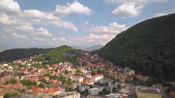 Aerial view of Brasov city, medieval town situated in Transylvania, Romania. Old architecture surrounded with big Carpathian mountains covered with dense green forest.