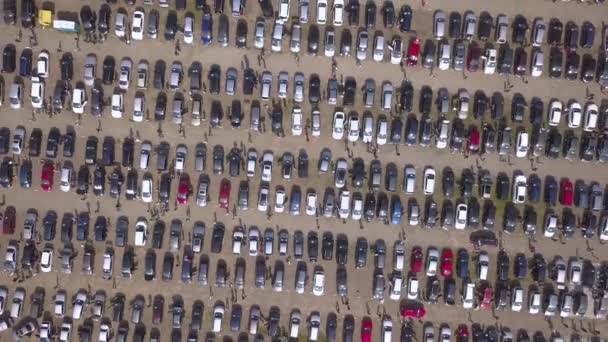 Aerial top view of many cars parked and people customers walking on car market or parking lot.