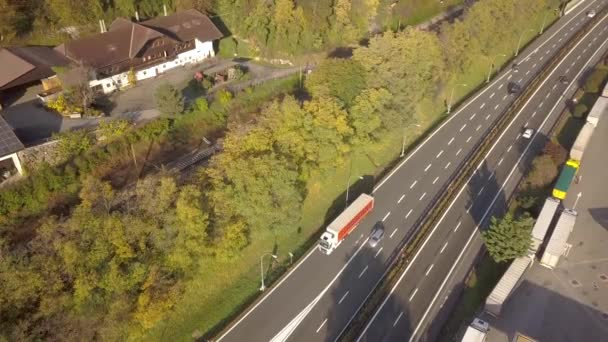 Top down vista aerea della strada interstatale autostradale con traffico in rapido movimento e parcheggio con autocarri parcheggiati.