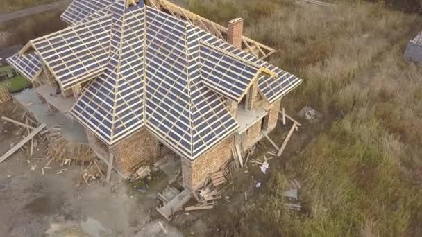 Letecký pohled na dům ve výstavbě. Nedokončená cihlová budova s dřevěným rámem pro střechu.