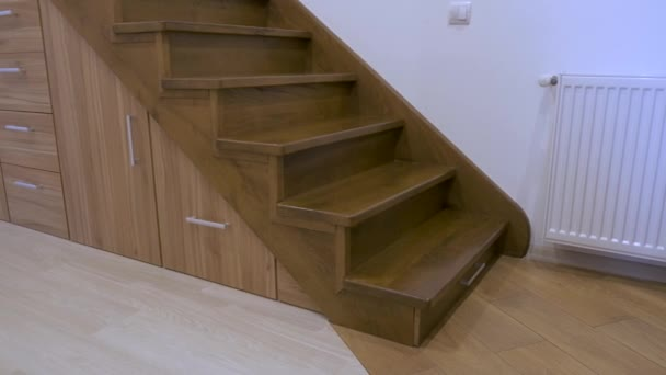 Interni di architettura moderna con corridoio di lusso con scale in legno lucido in casa a più piani. Armadi estraibili su misura su scivoli in fessure sotto le scale. Utilizzo dello spazio per larchiviazione.