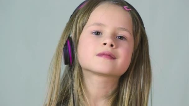Csinos mosolygós cild lány hallgat zenét nagy rózsaszín fülhallgató.