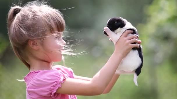 Hübsches Mädchen spielt im Sommer mit kleinen Welpen im Freien.