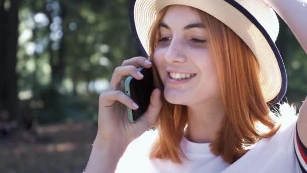Porträt eines hübschen Teenagers mit roten Haaren, Strohhut und rosa Kopfhörern, der im Park fröhlich mit dem Handy telefoniert.