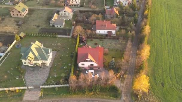 Kisváros vagy falu légi tájképe lakóházak és zöld fák soraival.