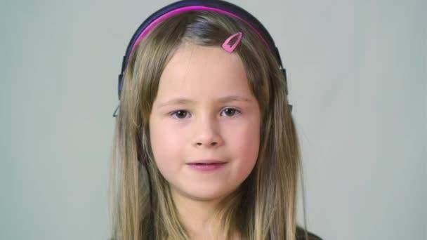 hübsches lächelndes Mädchen, das Musik in großen rosafarbenen Kopfhörern hört.