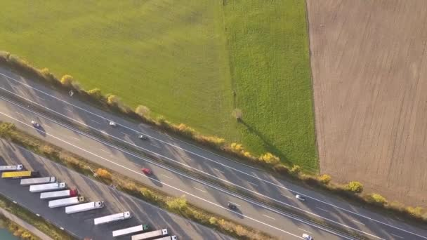 Top down aerial view of highway interstate road with fast moving traffic and parking lot with parked lorry trucks.