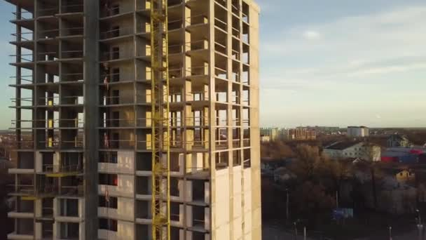 Aerial view of concrete frame of tall unfinished apartment building under construction in a city.