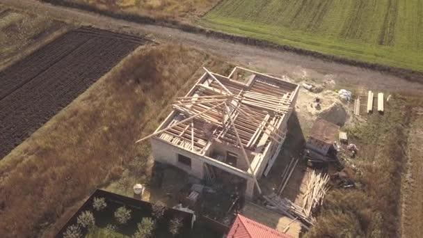 Von oben nach unten Luftaufnahme von zwei Privathäusern, eines im Bau mit hölzernem Dachstuhl und ein weiteres mit rotem Ziegeldach.