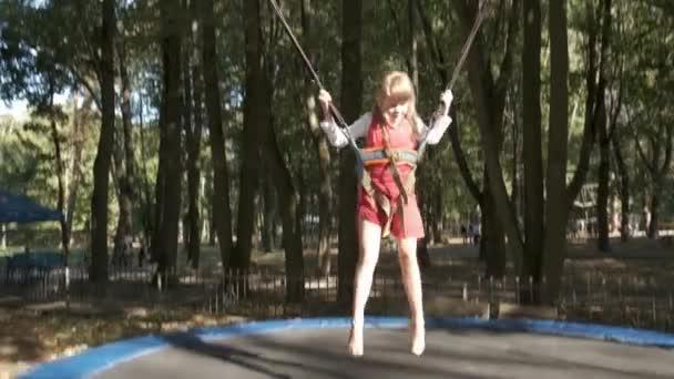 Mädchen springt im Sommerpark auf Trampolin.