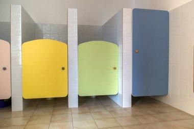 Colorful toilet doors in elementary school bathroom interior.