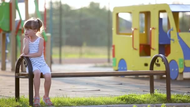 Aranyos gyermek lány vár anyja ül egy padon a nyári játszótér óvoda udvarán.