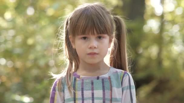 Portré boldog gyermek lány mosolyog a kamera világos homályos háttér.