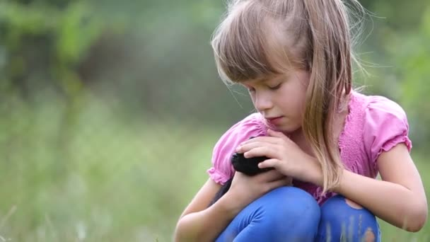 Pretty child girl playing with little puppy outdoors in summer.