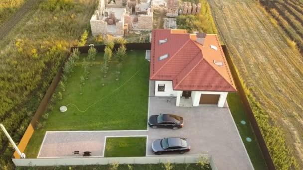 shora dolů letecký pohled na soukromý dům s červenou kachlovou střechou a prostorný dvorek s zaparkovanými dvěma novými vozy.