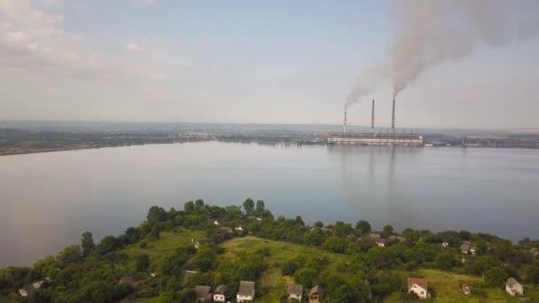 Letecký pohled na malou vesnici mezi zelenými stromy a velkým jezerem s vysokými komínovými trubkami znečišťující šedý kouř z uhelné elektrárny.