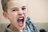 Szoros portré egy vicces dühös gyerek iskolás fiú nyitott mou