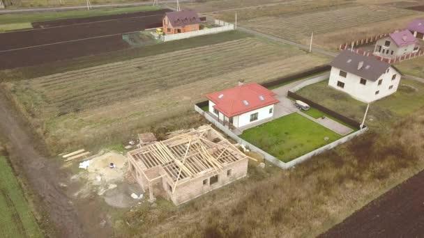 shora dolů letecký pohled na dva soukromé domy, jeden ve výstavbě s dřevěným zastřešovacím rámem a další zakončený červenou kachlovou střechou.