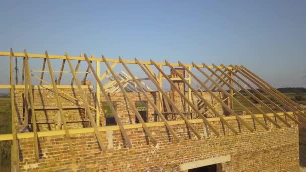 Luftaufnahme eines unfertigen Backsteinhauses mit Holzdachkonstruktion im Bau.
