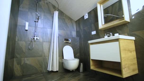 Interiér moderní stylové koupelny s černými kachlovými stěnami, sprchovým koutem a dřevěným nábytkem s umyvadlem a velkým osvětleným zrcadlem.