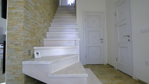 Stylové dřevěné moderní schodiště uvnitř podkrovního domu interiéru. Moderní chodba s dekorativními vápencovými zdmi a bílými dubovými schody.