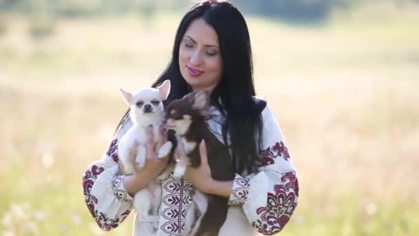Egy nő, aki két kiskutyát tart a karjában a szabadban..