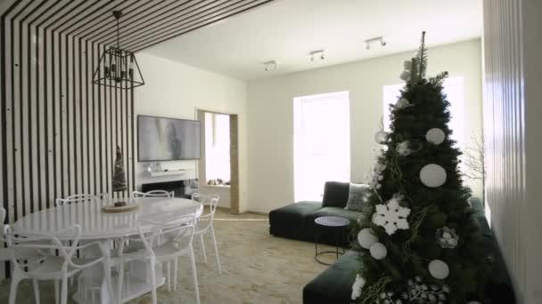 Interiér moderní prostorné kuchyně s bílými stěnami, dekorativními dřevěnými prvky, moderním nábytkem a velkým měkkým gaučem.
