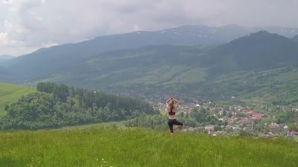 Mladá žena, která si v letním dnu užívá horského pohledu. Relaxace a meditace v přírodním prostředí.
