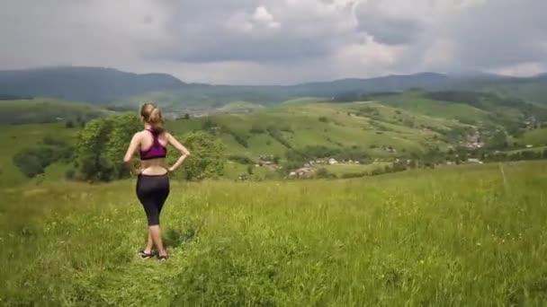 junge Frau genießt den Blick auf die Berge an einem Sommertag. Entspannung und Meditation in der Natur.