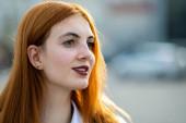 Szoros arckép egy mosolygós tinédzser lányról vörös hajjal és tiszta szemmel.