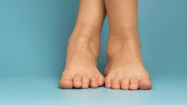 Zblízka bosé dětské nohy na modrém pozadí.