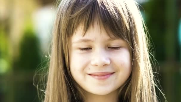 Portré csinos gyermek lány szürke szemekkel és hosszú szőke haj mosolygott a szabadban elmosódott zöld fényes háttér. Aranyos lány gyerek a meleg nyári napon odakint.