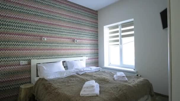 Interiér prostorného hotelového pokoje s čerstvým povlečením na velké manželské posteli. Útulný moderní pokoj v moderním domě.