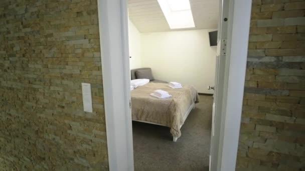 Interiér prostorného hotelového pokoje v podkroví s čerstvým ložním prádlem na velké manželské posteli. Útulný moderní mansard pokoj v moderním domě.