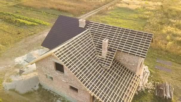 Letecký pohled na nedokončený dům s dřevěnou střešní konstrukcí potaženou kovovými dlaždicemi ve výstavbě.