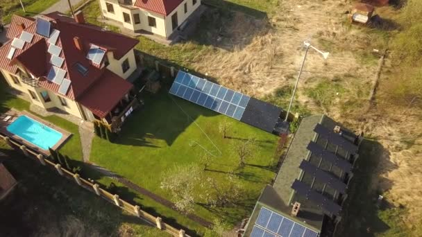 Aerial view of a private house with green grass covered yard, solar panels on roof, swimming pool with blue water and wind turbine generator.