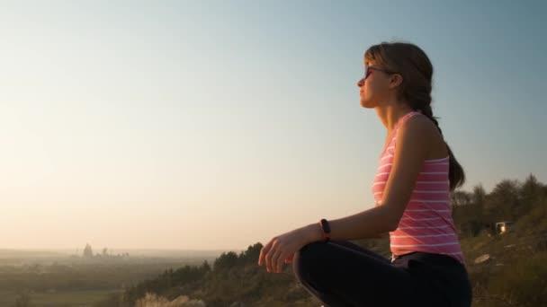 Mladá uvolněná žena sedí venku na velkém kameni a užívá si teplého letního dne. Dívka meditující a relaxující na přírodě při západu slunce.