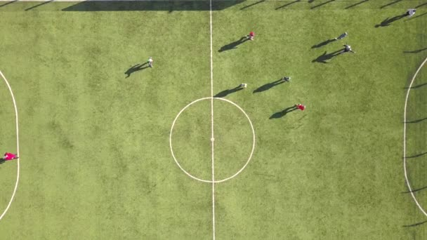 Top down aerial view of green football sports field and players playing football. Small unrecognizable sportsmen on grass covered stadium during sport activities.