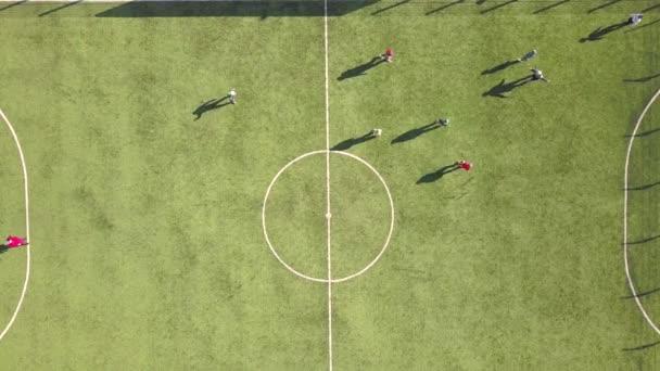 Felülről lefelé légi kilátás a zöld labdarúgó sportpálya és a játékosok foci. Kis felismerhetetlen sportolók a fűvel borított stadionban sporttevékenységek során.