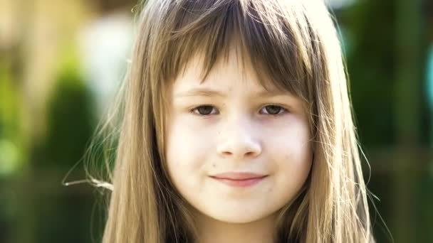 Portrait of pretty child girl with gray eyes and long fair hair smiling outdoors on blurred green bright background. Cute female kid on warm summer day outside.