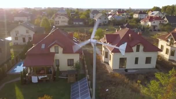 Letecký pohled na obytný soukromý dům se solárními panely na střeše a větrné turbíně.