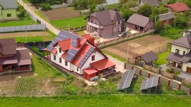 Letecký pohled na dům v rezidenční čtvrti se solárními panely na střeše.
