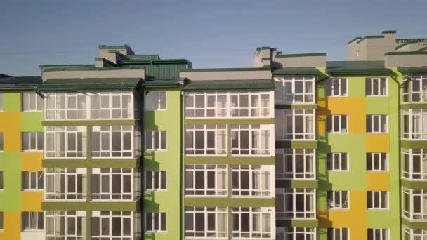 Luftaufnahmen eines hohen Wohnhauses mit vielen Fenstern und Balkonen.