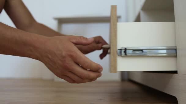 Großaufnahme männlicher Tischlerhände, die Möbelschränke zusammenbauen und hölzerne neue Schubladen einbauen.