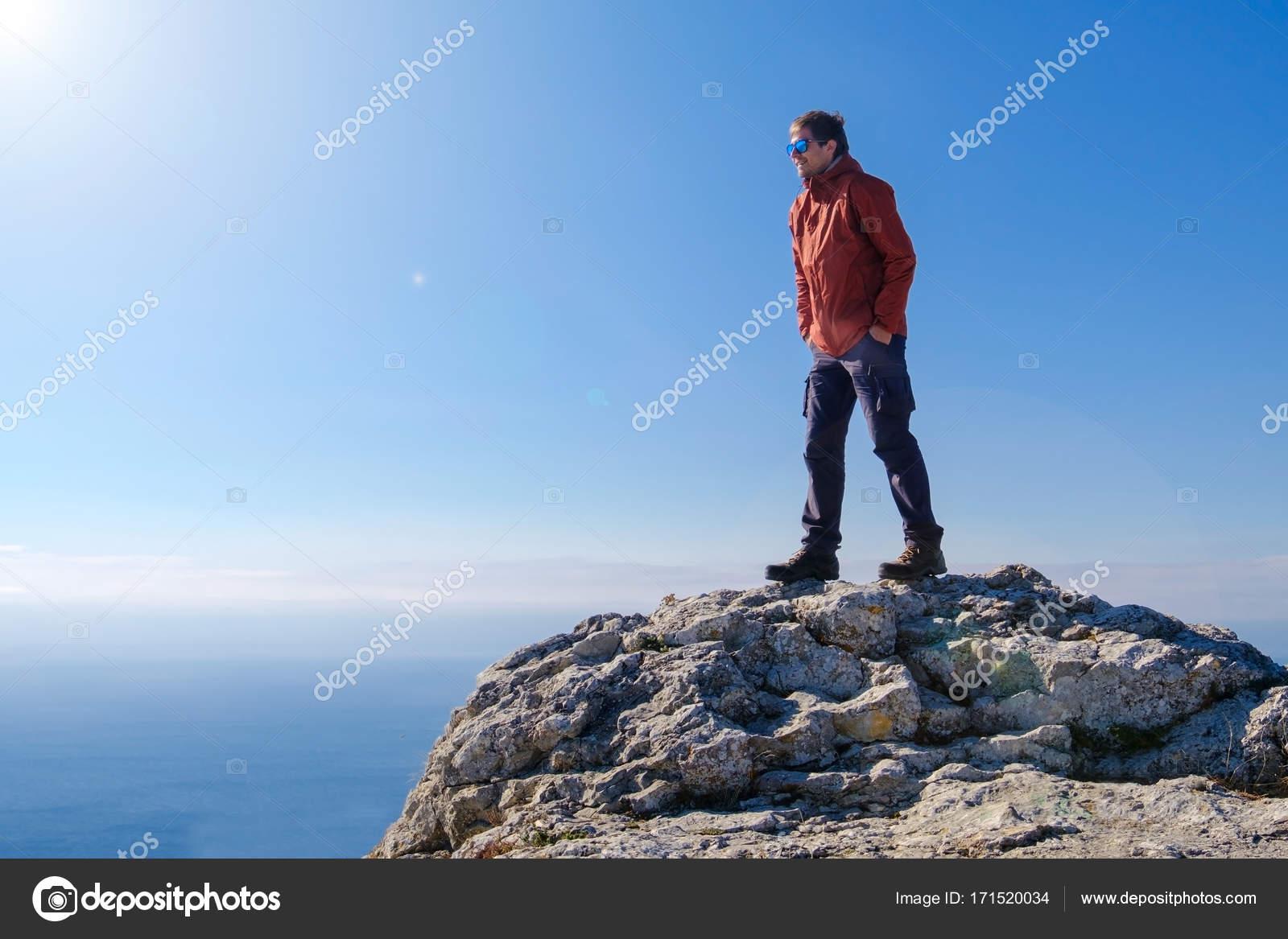Homem sorridente em óculos de sol em pé no pico da montanha de pedra. Luz  do dia — Fotografia por ruzvold.mail.ru 4ce2e2d657