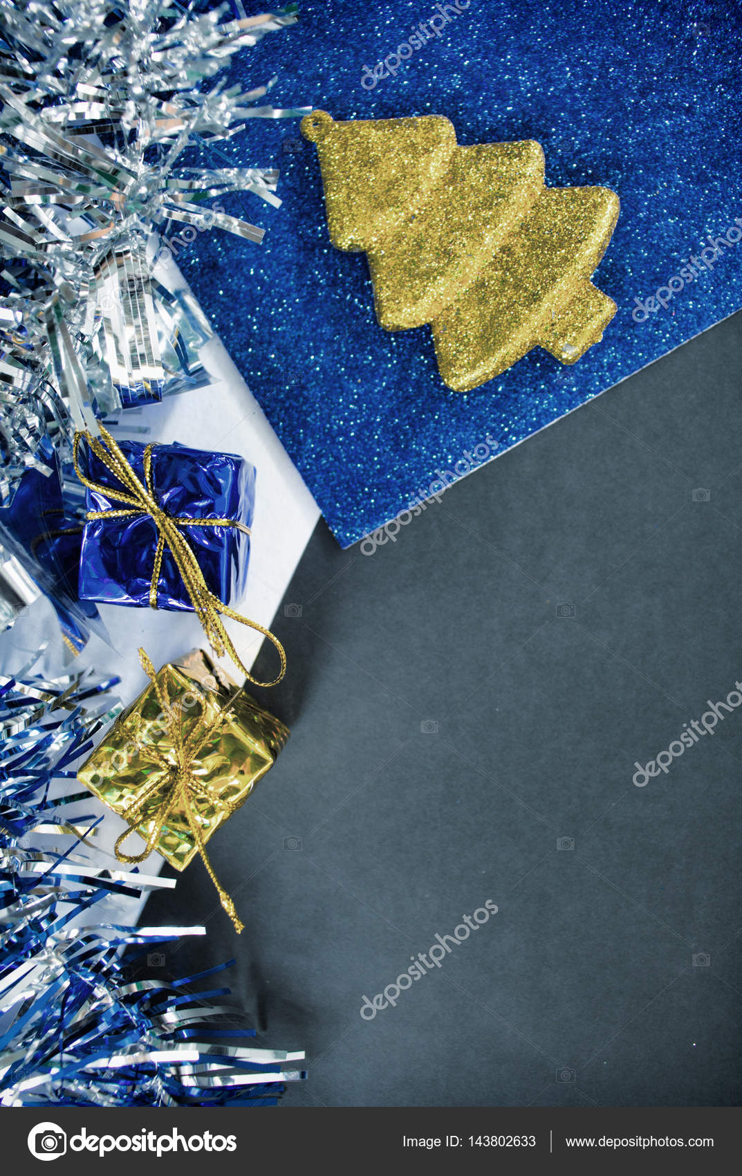 Toned photo of Christmas decor and black paper for greeting message.  Christmas card or banner template. Christmas decor vertical image. Blue and  gold ...
