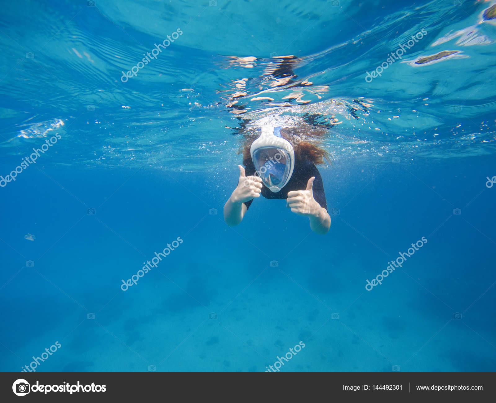 990bed941 Snorkel feminino em máscara facial e nade engrenagem. Retrato subaquático  de natação garota mostrando os polegares. Mergulho no mar tropical.