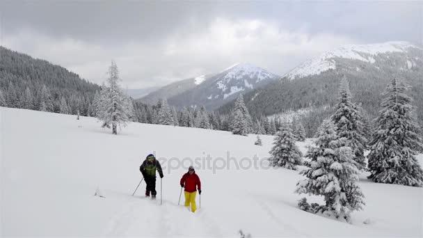 Dvojice cestujících jde na sněžnicích
