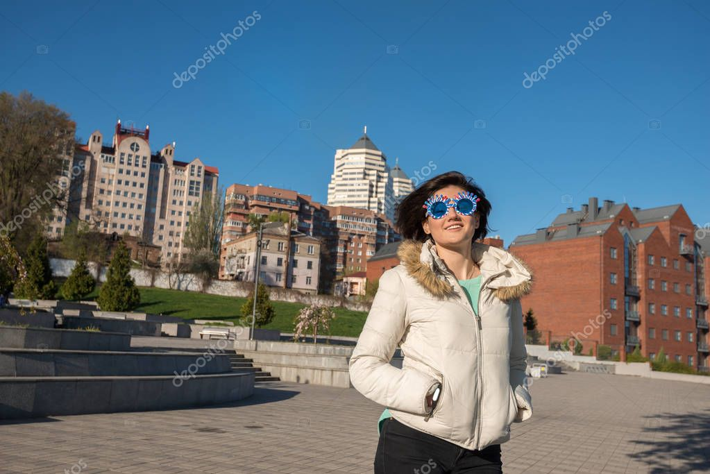 Portrait of a smiling girl in a funny sunglasses with flying hai